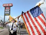 Veteran Marches while holding flag